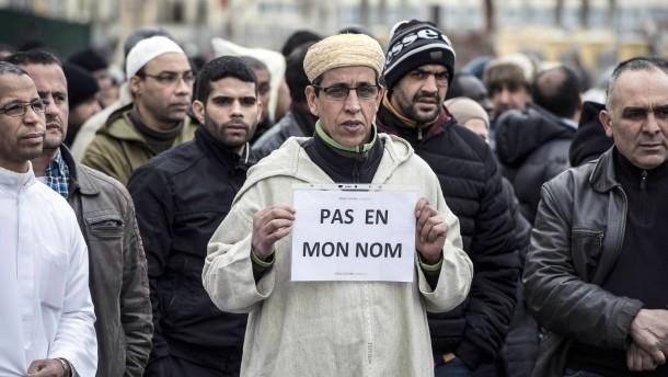 """Ein französischer Muslim hält am 9. Januar in Saint-Etiennevor einer Moschee ein Schild mit der Aufschrift """"Nicht in meinem Namen"""", um gegen den Anschlag von Paris zu protestieren. Muslime die an Allah den Barmherzigen glauben und Barmherzigkeit in ihren Herzen haben wollen. Früher nannte man Muslime Mohammedaner. Sind radikale Islamisten mehr Mohammedaner? Mohammed hat zu seiner Zeit schon einen Islamischen Staat angefangen aufzubauen."""
